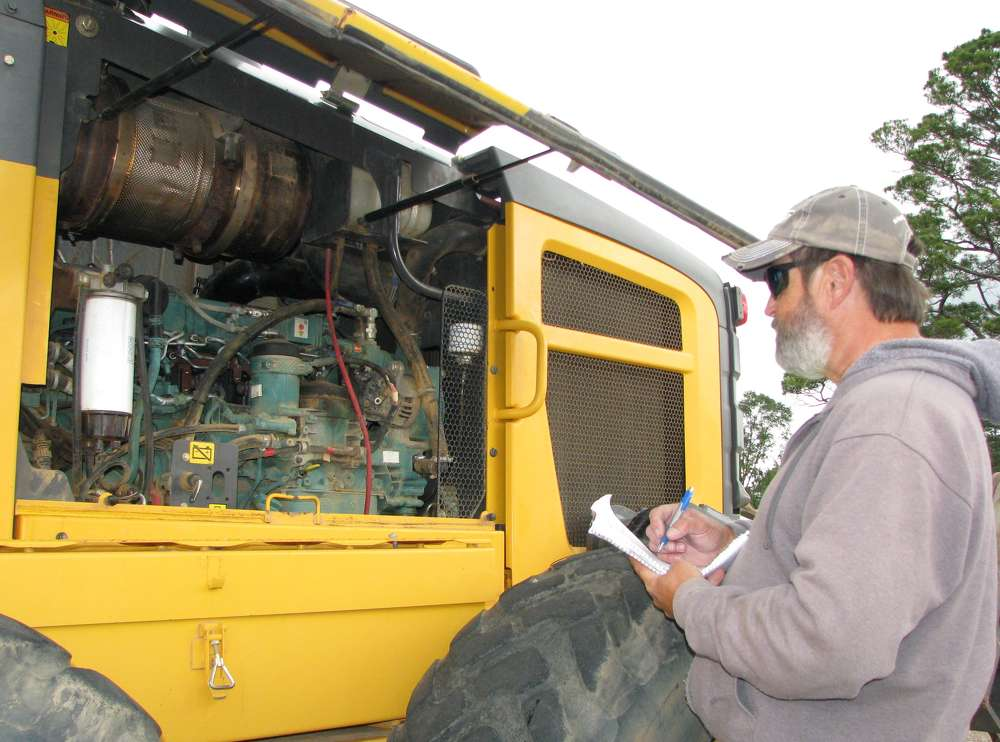 Jotting some final notes before bidding on a Volvo G930B motorgrader is Mark Trahan of Denmar Equipment, Sulphur, La.