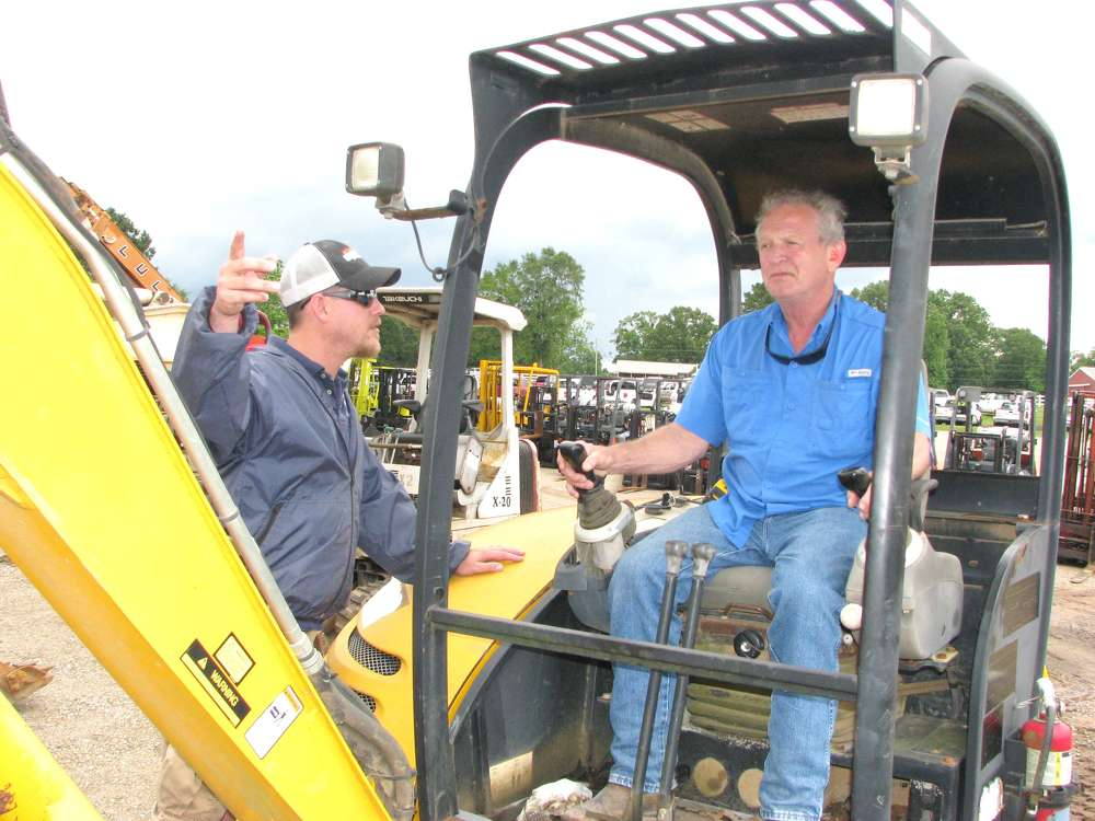 Matt McNeil (L) and his dad, Phillip, of McNeil Cabinet Millworks, Bay Spring, Miss., were very interested in this JCB 8045zts mini-excavator.