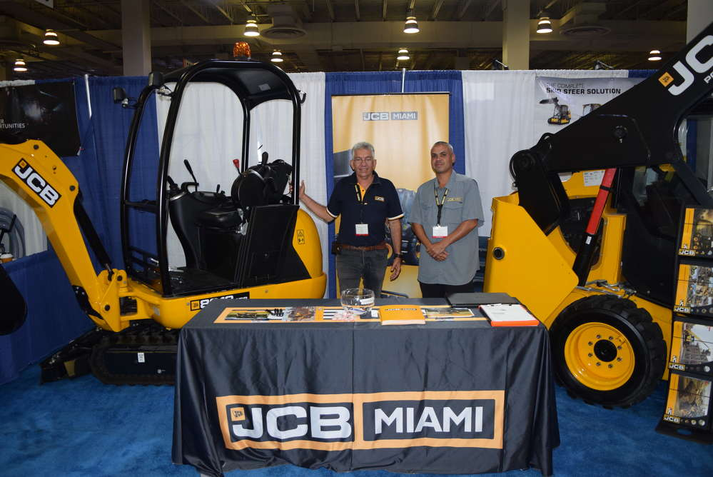 Elio Leon (L) and Kenneth Lemus, both of JCB Miami, discuss the JCB 8018 CTS mini-excavator and the  JCB 190 skid steer.