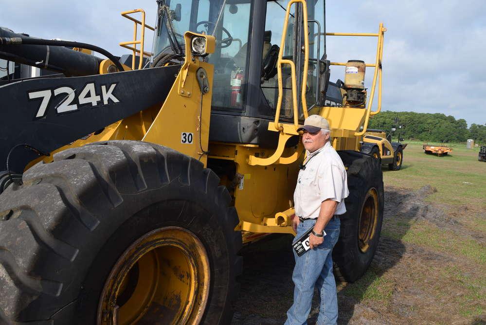 Pudge Guttler of Guttler Bros Equipment in Ft. Pierce, Fla., inspects this John Deere 724K wheel loader before the auction.