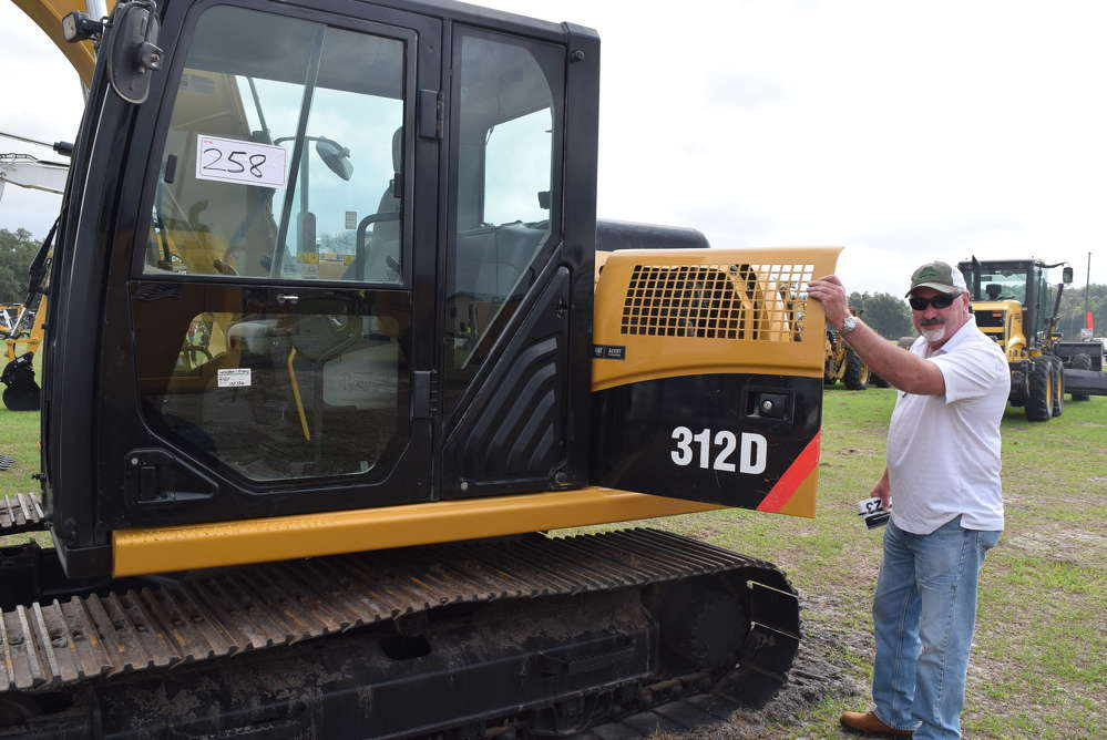 Tim Sheehan of QGS Construction in Tampa, Fla., inspects the engine of this Cat 312D excavator before he started to bid on it