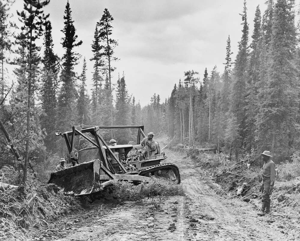 Crews use a Caterpillar tractor with grader to widen the roadway in 1942 during construction of the Alcan.
