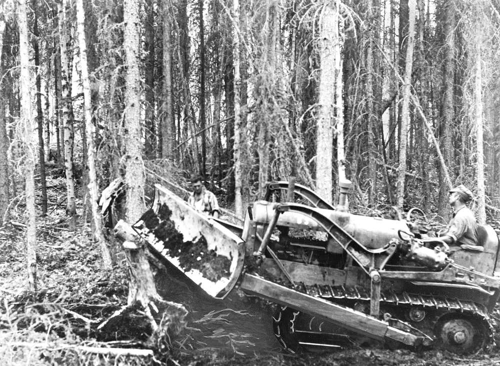 A bulldozer knocks down trees, cutting the roadway in 1942. (Library of Congress photo)