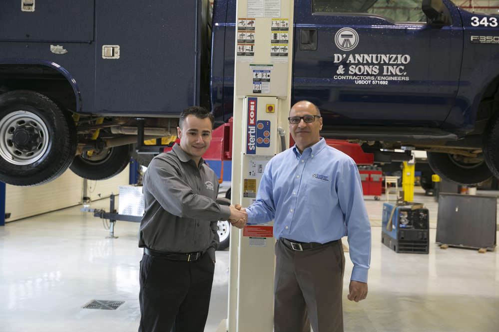 Matthew Morgan (L), principal at Stertil-Koni distributor, Hoffman Services and John Cafro, equipment manager at D'Annunzio & Sons, shake hands while standing in front the of two-post Freedom.