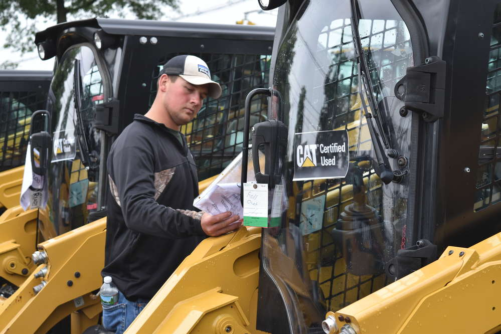James Koller (L), foreman of First Rate Landscape, Morristown, N.J., checks out the price tag of a Caterpillar skid steer.