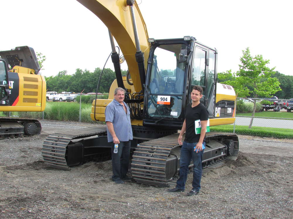 Steve Long (L) and Chris Empire, both of Equipment Rental, Ronkonkoma, N.Y.,  consider bidding on three Cat 320D L hydraulic excavators at the auction.
