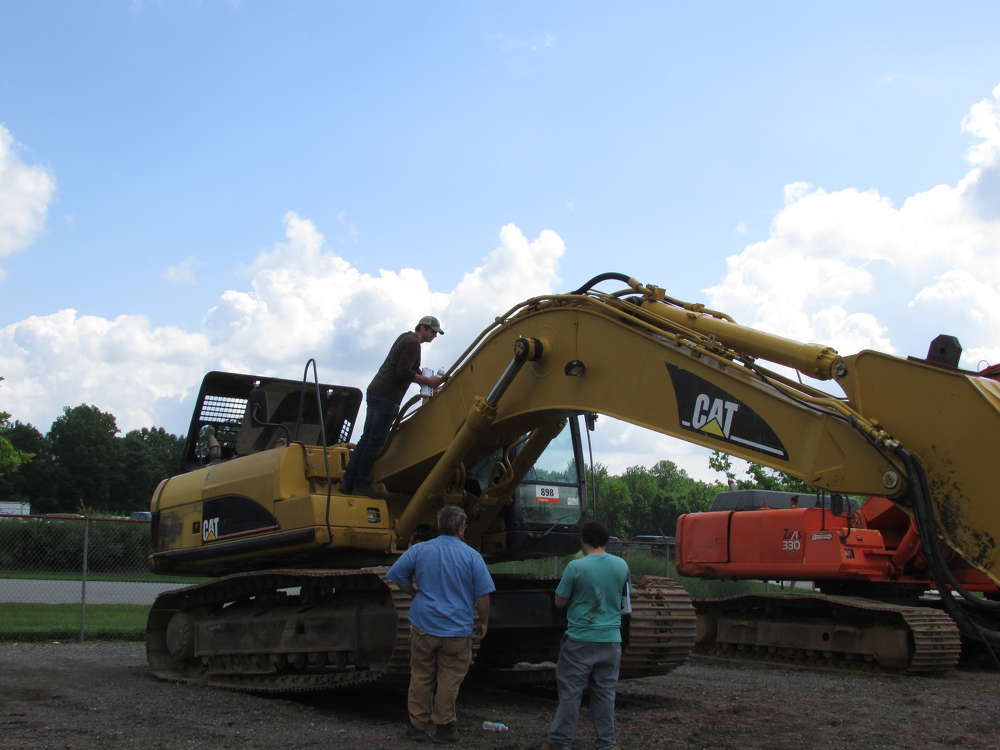 George Nogueiras, sales manager, Newark Equipment Sales Corp., inspects this Cat 330CL hydraulic excavator.