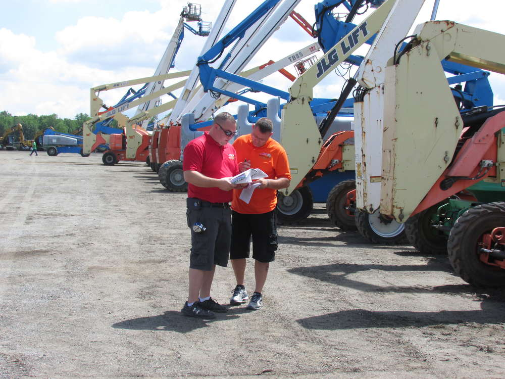 Nathan McCutcheon (L) and Jason Joseph, both of MEI Enterprises Inc., Apollo, Pa.,  look over their notes at the auction.