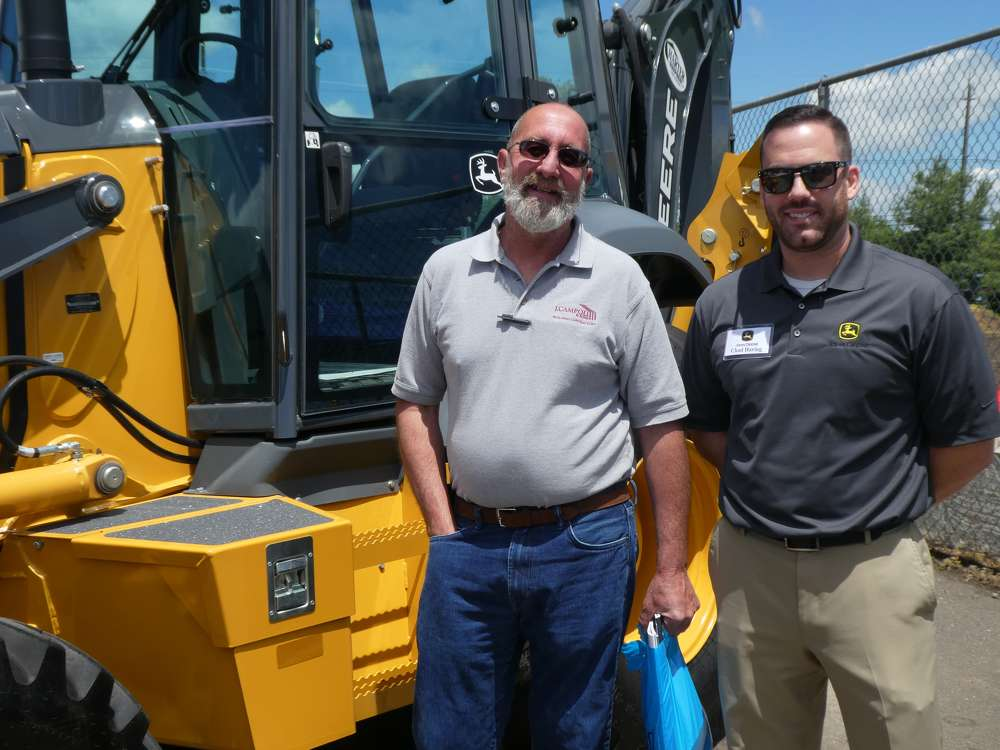 Looking over a John Deere backhoe are Gary Reinfried (L) of J. Campoli & Sons, Cresskill, N.J., and Chad Haring, John Deere territory sales manager.