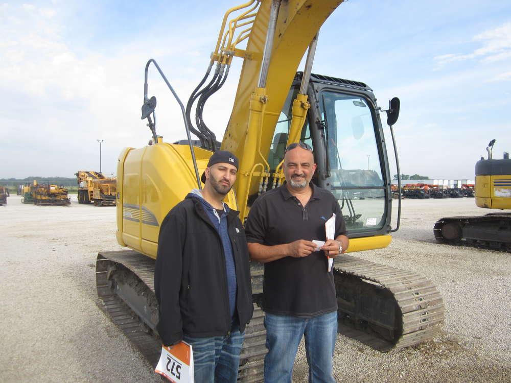 Mo Dari (L) and Rami Abbasi, both of Abbasi Equipment, stand in front of this Kobelco SK140SR excavator.