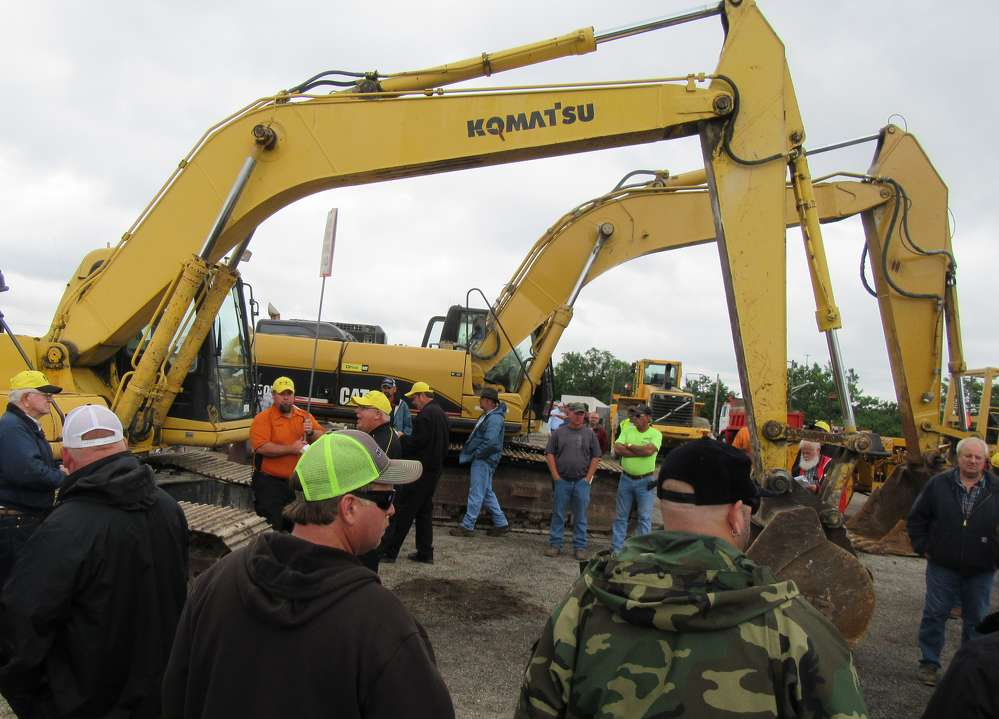 Attendees compete for the winning bid on these excavators at the auction.