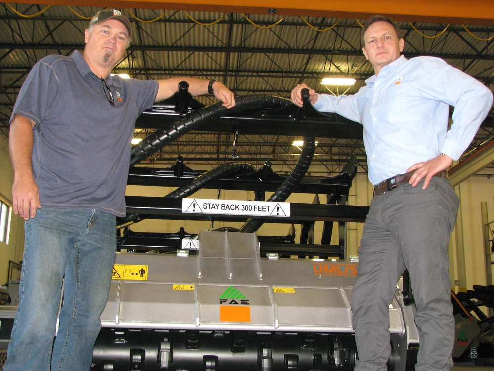 Edwin McCain (L) and Giorgio Carera look over the new mulching heads, like the ones that McCain uses in his own business, at the warehouse facility of FAE USA in Georgia.