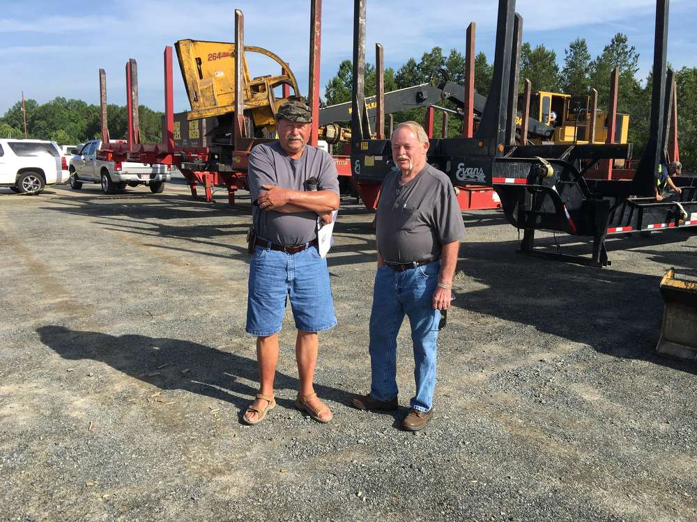 Natt Black (L) of Natt Black Logging Inc. in Ansonville, N.C., and Mike Goodwin of JWG Land & Timber Inc. in Lilllesville, N.C., look over the logging trailers.