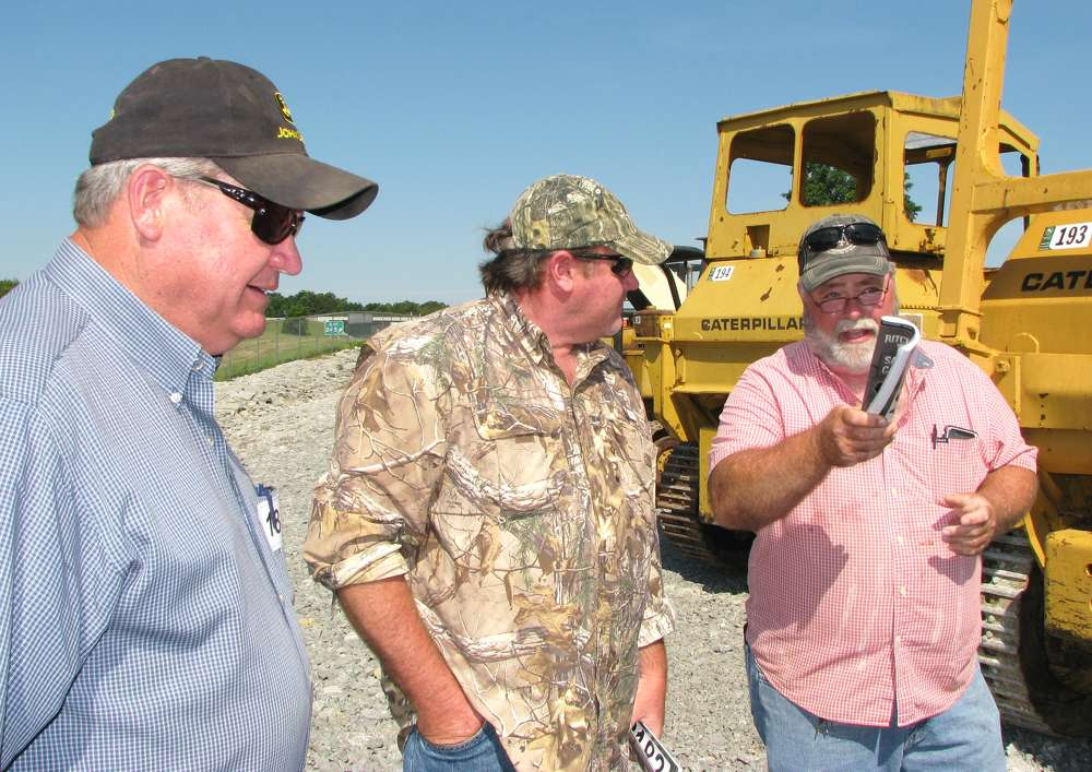 (L-R): Terry McPeak, local farmer; Mark Gheen, Gheen Construction, Knoxville, Tenn.; and Tommy Grissom, Grissom Excavating, Carthage, Tenn., discuss some of the dozers about to go on the auction block.
