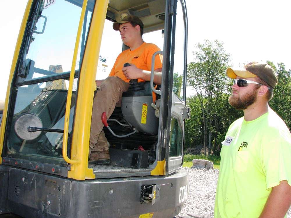 Josh (L) and Joel Passons, both of Passons Construction, Sparta, Tenn.,  test operate a Volvo ECR88 mini-excavator.