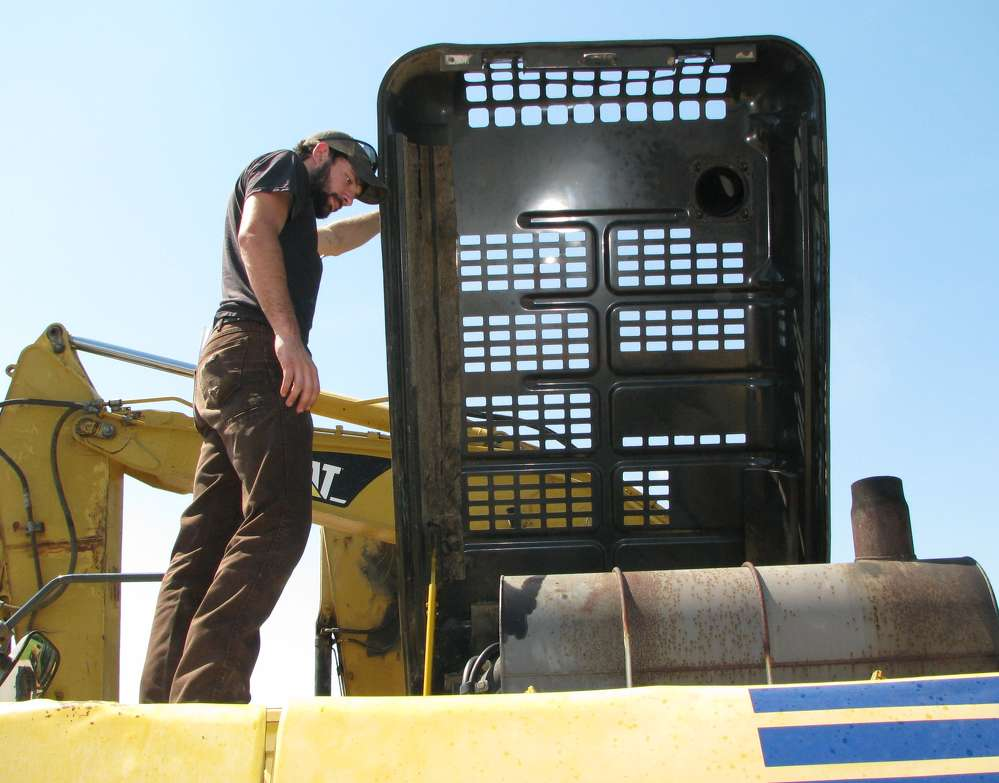 Charles Biles of Biles Transport, Rock Island, Tenn., wraps up an inspection of a Komatsu PC300LC excavator.