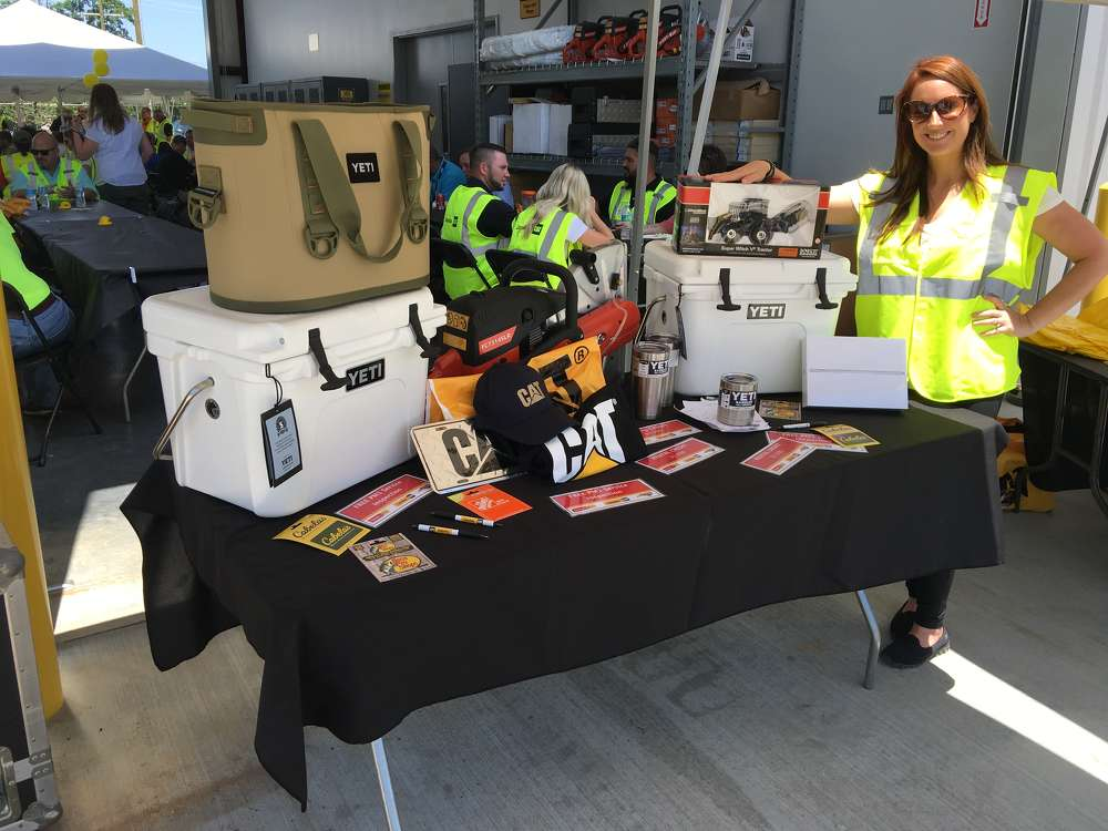 The company gave away a table full of gifts, including gift certificates, Yeti coolers, Cat merchandise, $1,000 rental credits and more.  Nikki Smith of Carolina CAT answers questions and registers guests for the prizes.