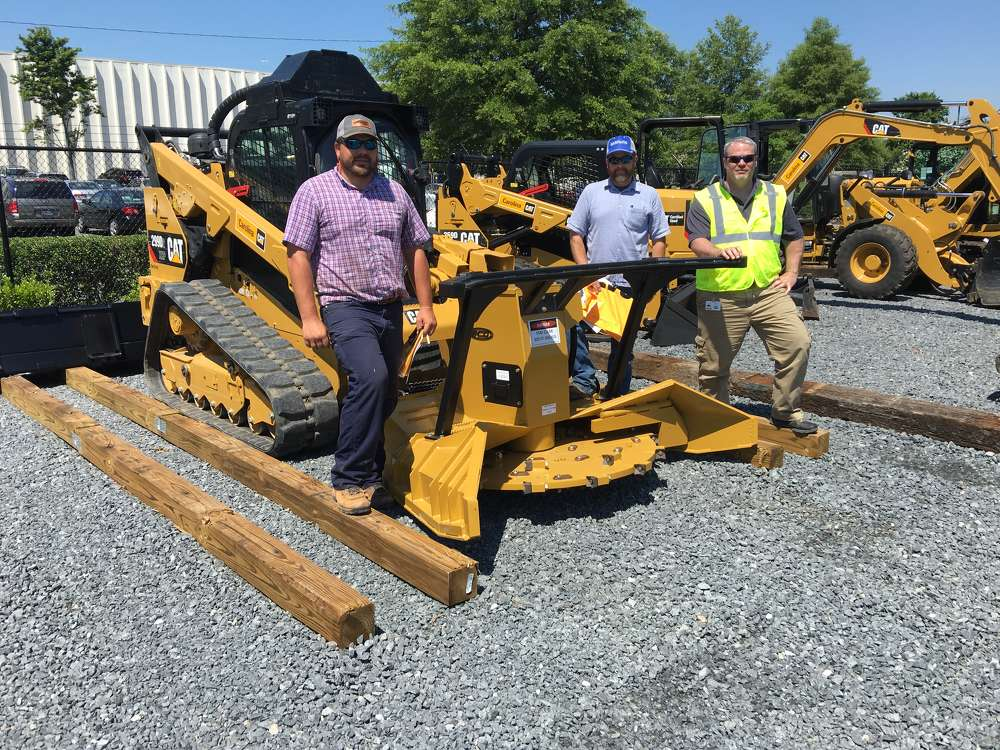 Logan Hardin and Bryan Amick, both of Carolina Wetland Services in Charlotte, N.C., and Craig McCoy of Carolina CAT talk about the Cat 299D with an Eco Mulcher attachment.