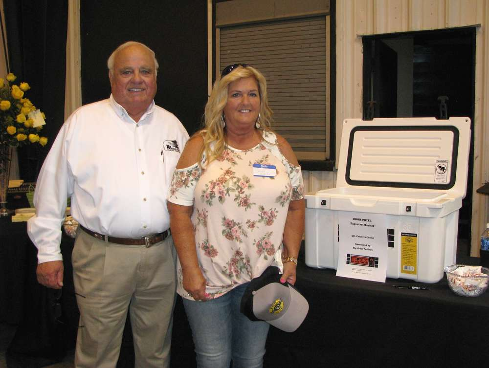 Gene Taylor (L), owner of Warrior Tractor, presents one of the prize drawings, a Calcutta cooler, to Danna Martin of David Martin Logging, Nauvoo, Ala.