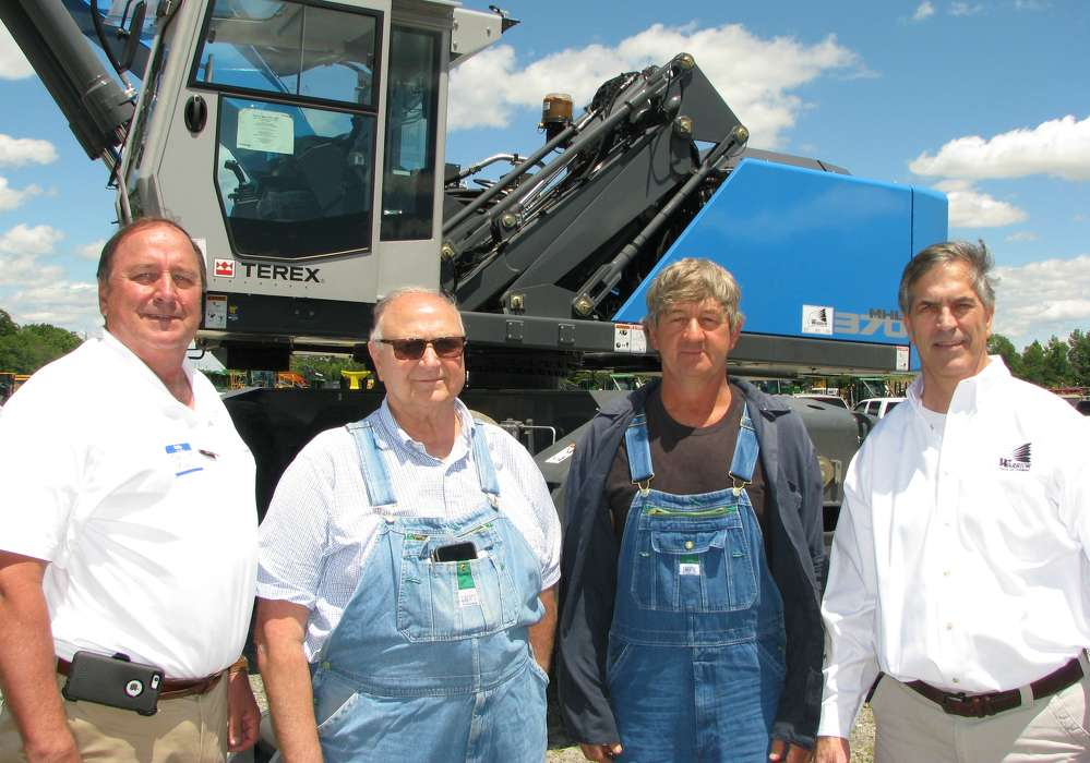 (L-R): John Van, Terex Fuchs, Louisville, Ky., talks with the new owners of this Fuchs MHL370F, Frank Cicatiello and Henry Miller, both of Liberty Recycling, Tuscaloosa, Ala.; and Jeff Dupre, Warrior Tractor.