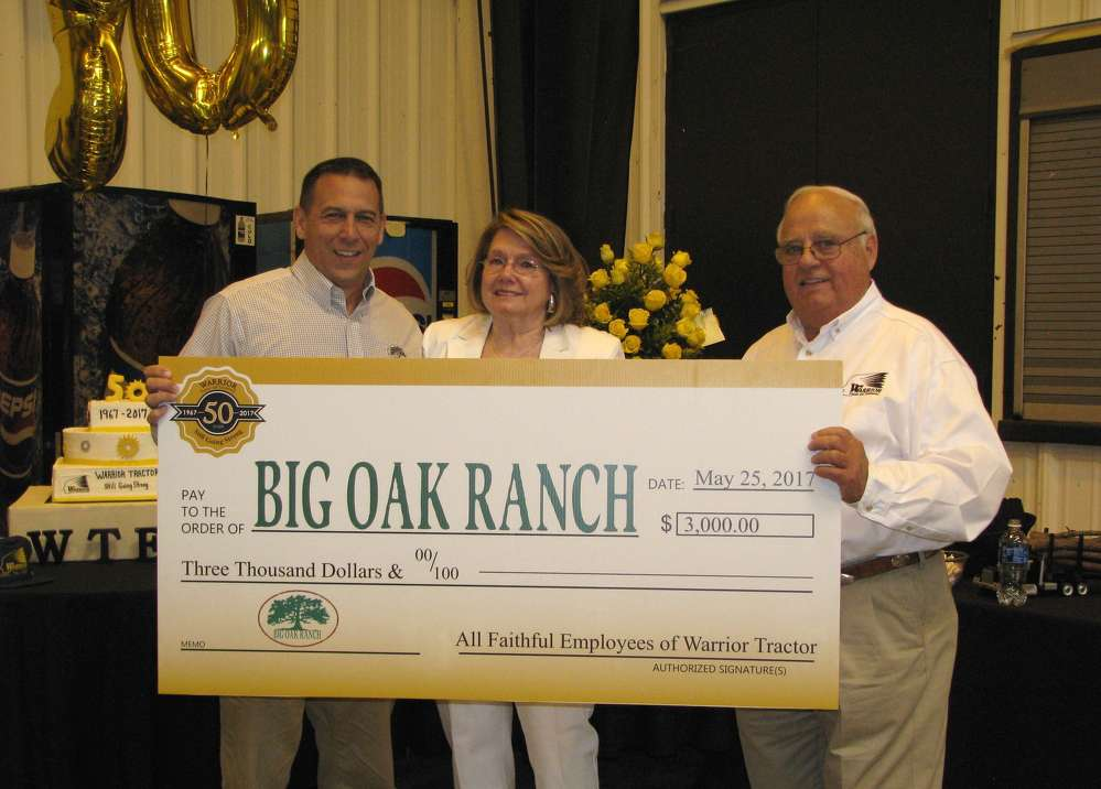 Employees of Warrior Tractor raised money for one of the Taylor's favorite charities to commemorate the 50th anniversary. (L-R): Tony Osborne, director of Big Oak Girls Ranch holds a check in the amount of $3,000, which was donated in the name of Warrior owners Glennette and Gene Taylor.