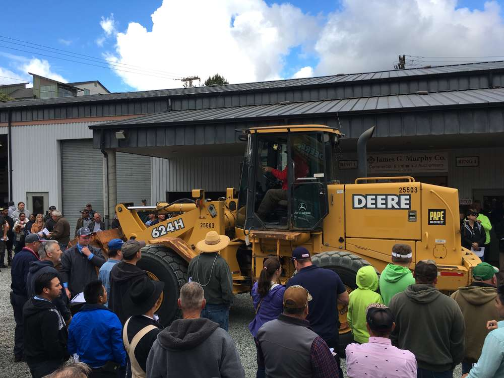 The crowd sees one of four John Deere 624H wheel loaders sold at the auction.