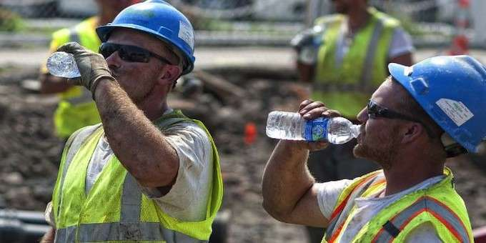 Workers in hard hats and vests labored in the heat and try to stay hydrated. (eSUB Construction Software photo)
