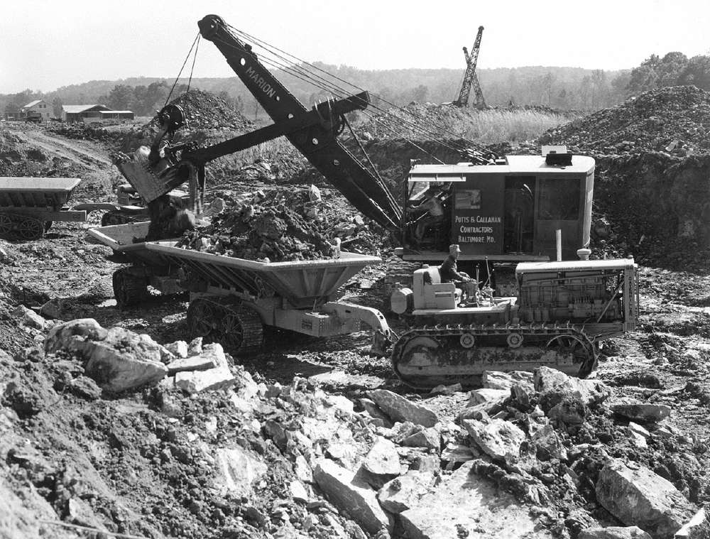 Potts & Callahan used a Marion power shovel to load rock and dirt into tandem Athey tracked dump wagons pulled by Caterpillar RD-8 tractors. The photo was taken during October 1937.