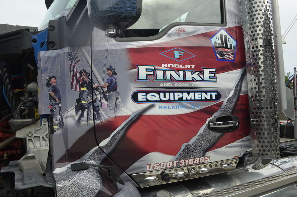 The door panels feature the iconic image of three firefighters raising the American flag during the rescue efforts.