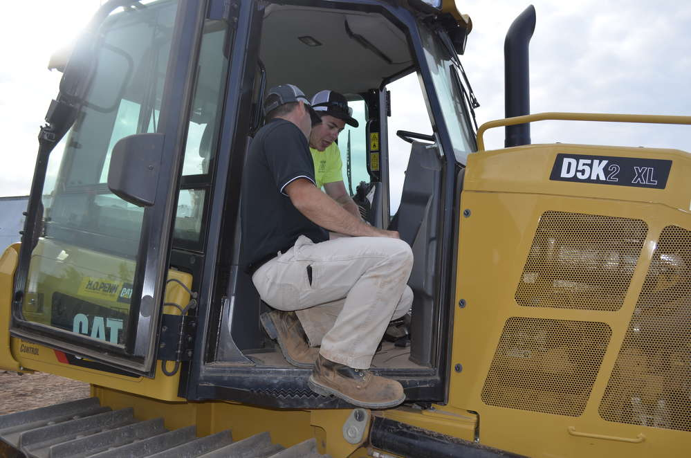 A member of the SITECH Metro Northeast team introduces a customer to the GPS technology available in the Cat D5K.