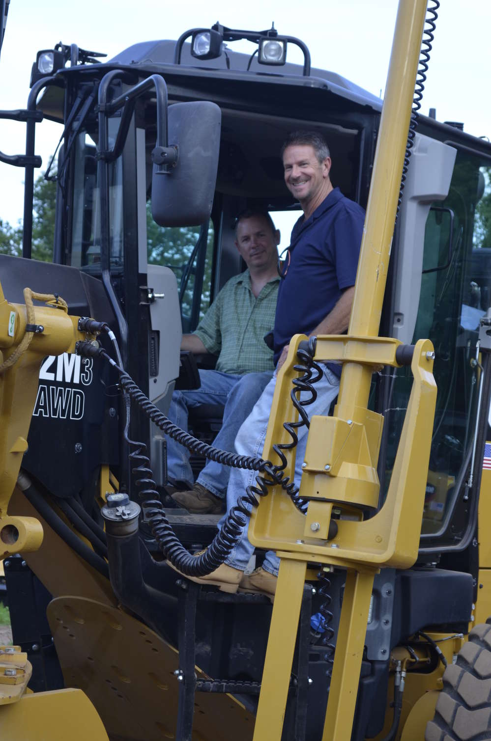 Bob Lodge (in cab) of Lodge Earthworks, Windsor, Conn., and Richard Roulstor of Roulstor Services, Windsor Locks, Conn., were very impressed with the controls of the Cat 12M motorgrader.