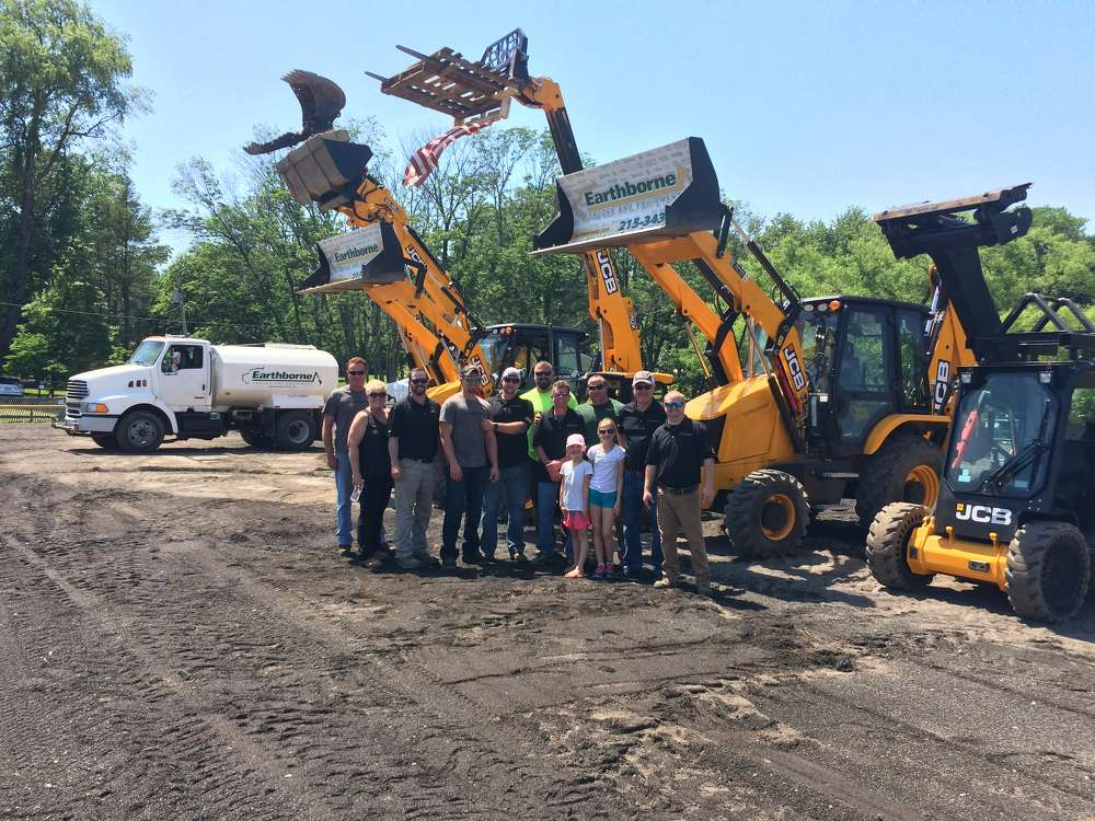 Doug Taylor (3rd from L), son of founder and vice president of Earthborne JCB, and the team who brings the Dancing Diggers to life, prepare for another show at the June Fete.
