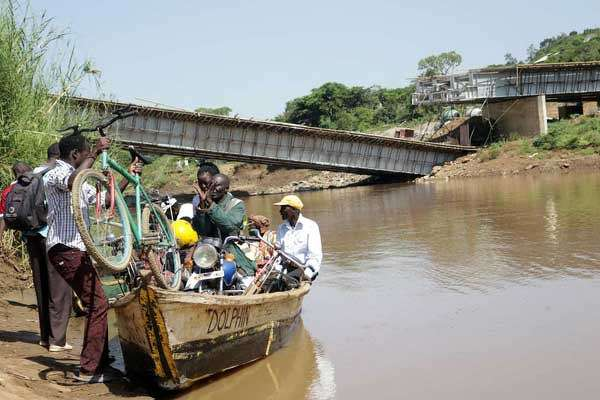 Resident cross River Nzoia using a boat on June 27, 2017 after Sigiri Bridge in Budalang'i collapsed.  (Tonny Omondi | Nation Media Group photo)