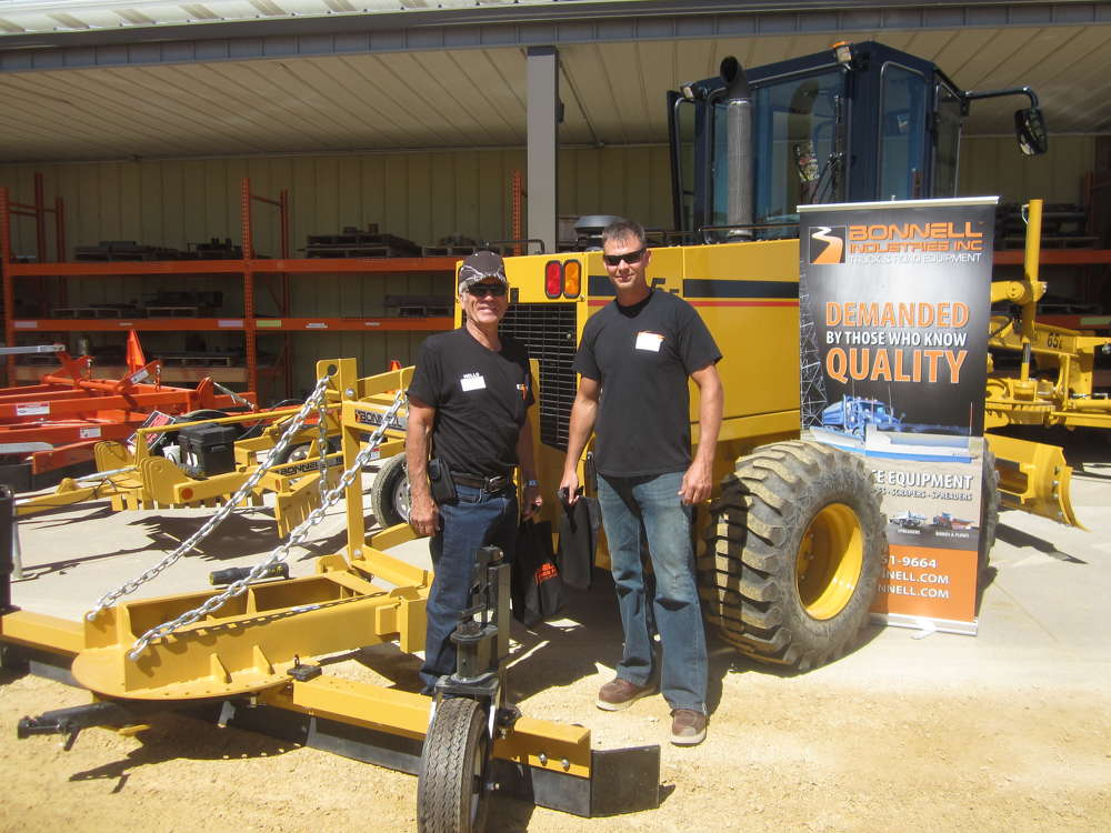 Lee Berndt (L) and Jason Galus, both of Homer Township Highway Department, look over the NorAm 65 grader equipped with a Bonnell Industries windrow eliminator.
