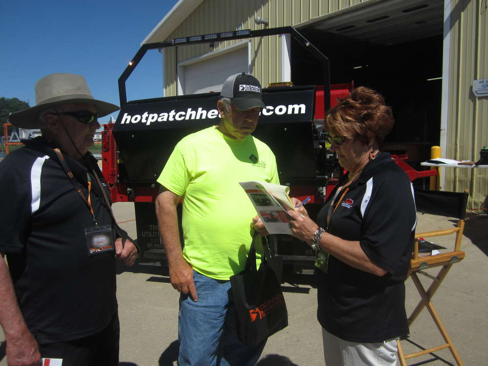 Jim Knauer (C), Elizabeth Township, learns more about the hot patch heater manufactured by Five D Industries from Stu Lemke (L) and Sheila Pudelko, both of Five D industries LLC.