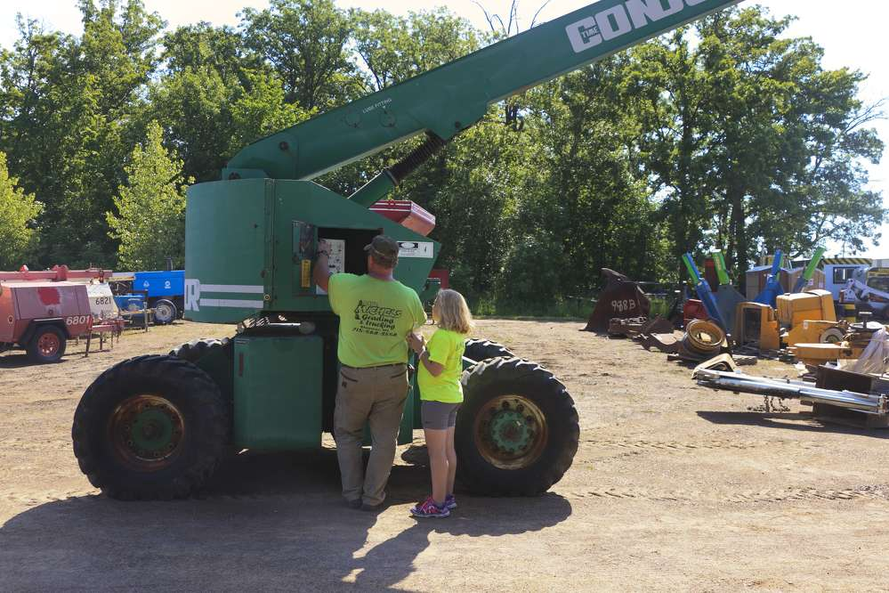 A father and daughter team inspect a Condor T60Q8 boom lift.