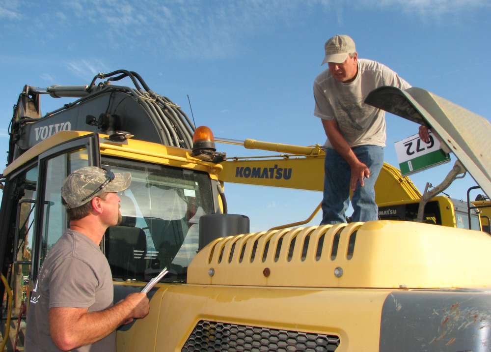 Troy Motz (L) of Troy Motz Construction, Lincolnton, N.C., and Kenny Carpenter of Lincoln County Fabricators, also in Lincolnton, N.C., inspect a Volvo EC220 excavator.