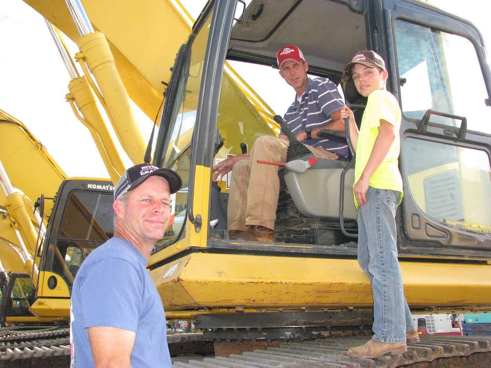 Paul (L) and  Garrett Rivers (R), both of Rivers Grading, Fayetteville, Ga., and Matt Neely, Matt Neely Homes, Sharpsburg, Ga., get a closer look at this Komatsu PC350 excavator.
