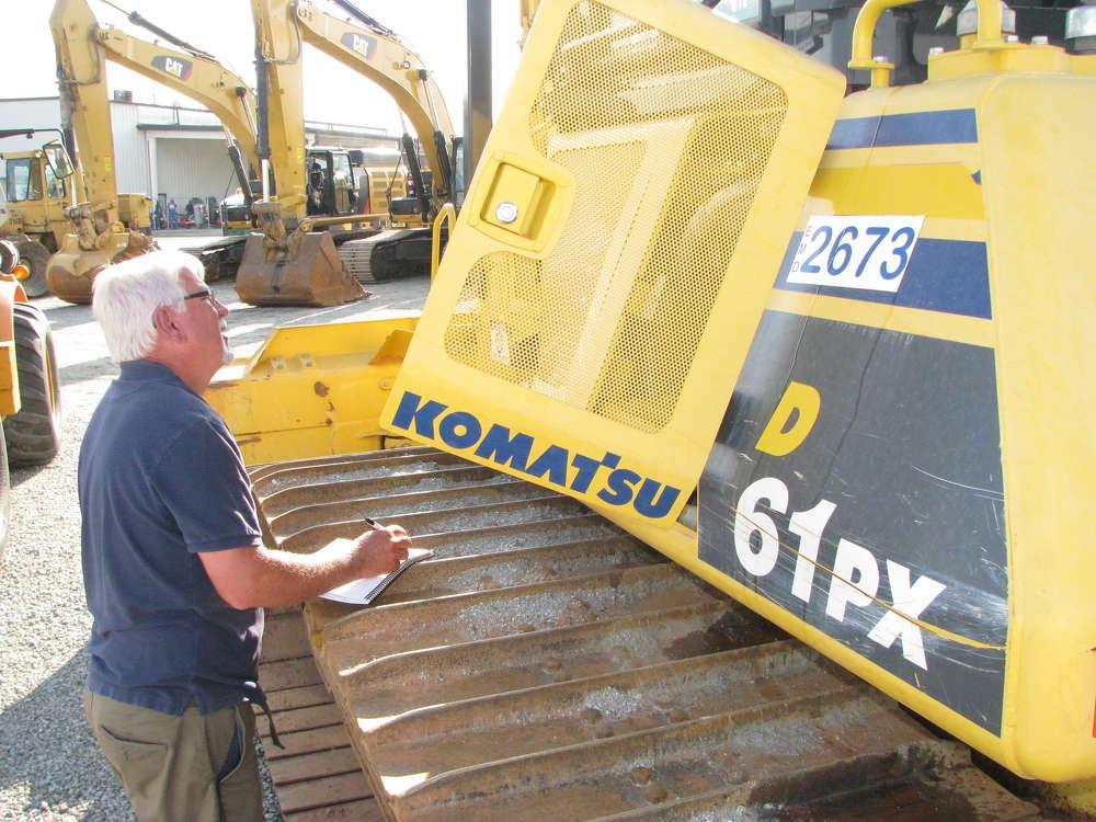 Skip Walker of High Hills Equipment, Ellijay, Ga., jots some notes before bidding on a Komatsu D61PX dozer.