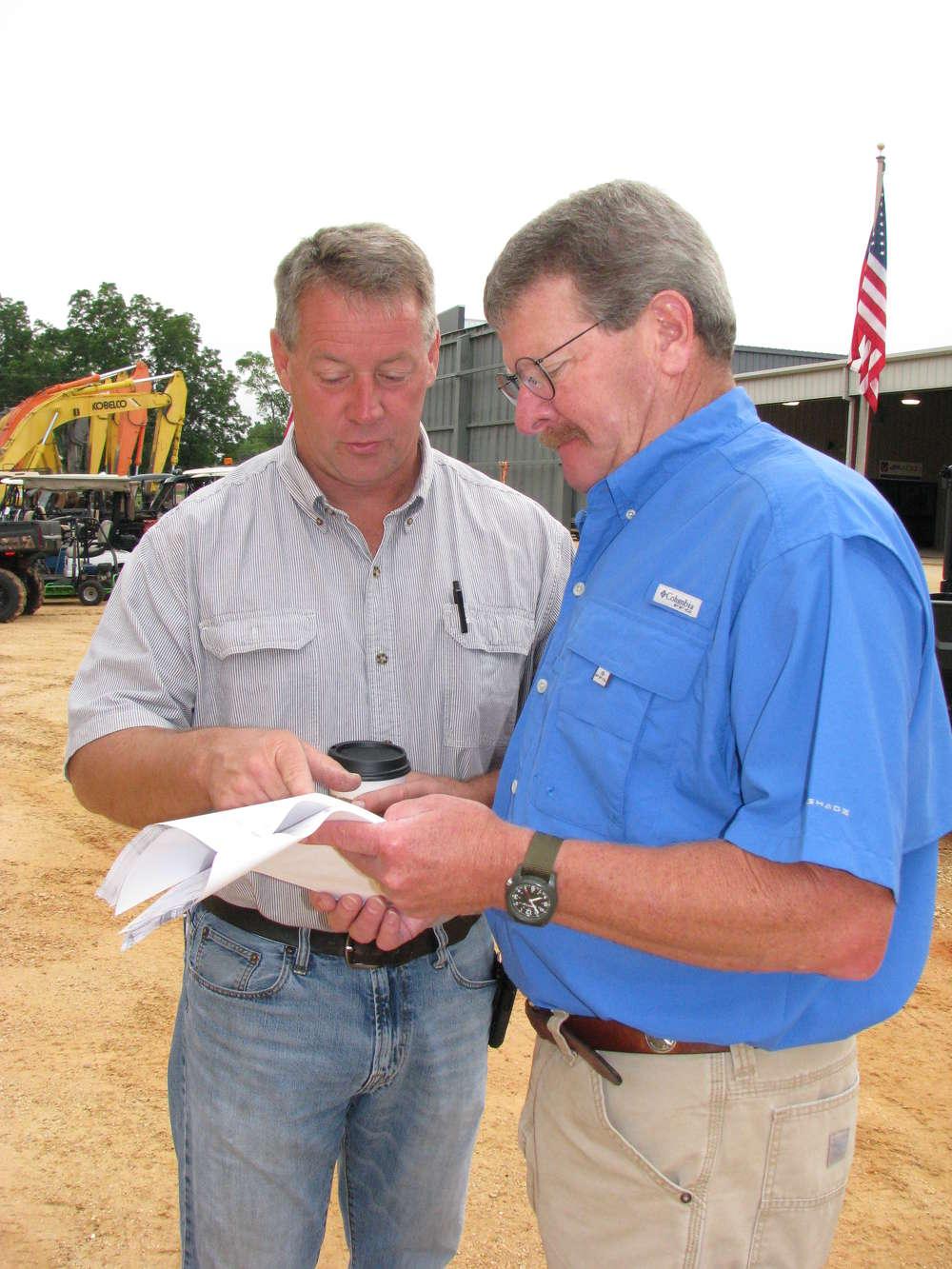 Bill Woods (L) of Woods Equipment, Nashville, Tenn., asks Phil Lucius, JM Wood, a question.