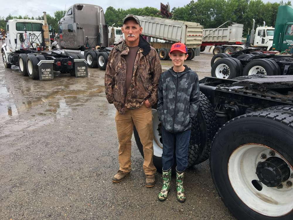 Gary (L) and Evan Justice of Gary Justice Grading in Mt. Rest, S.C., show interest in the road tractors and dump trucks.