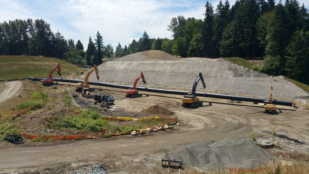Five excavators — four John Deeres and one Hitachi — lift a 310-ft.-long stormwater pipe into a trench. (Ceccanti Inc. photo)