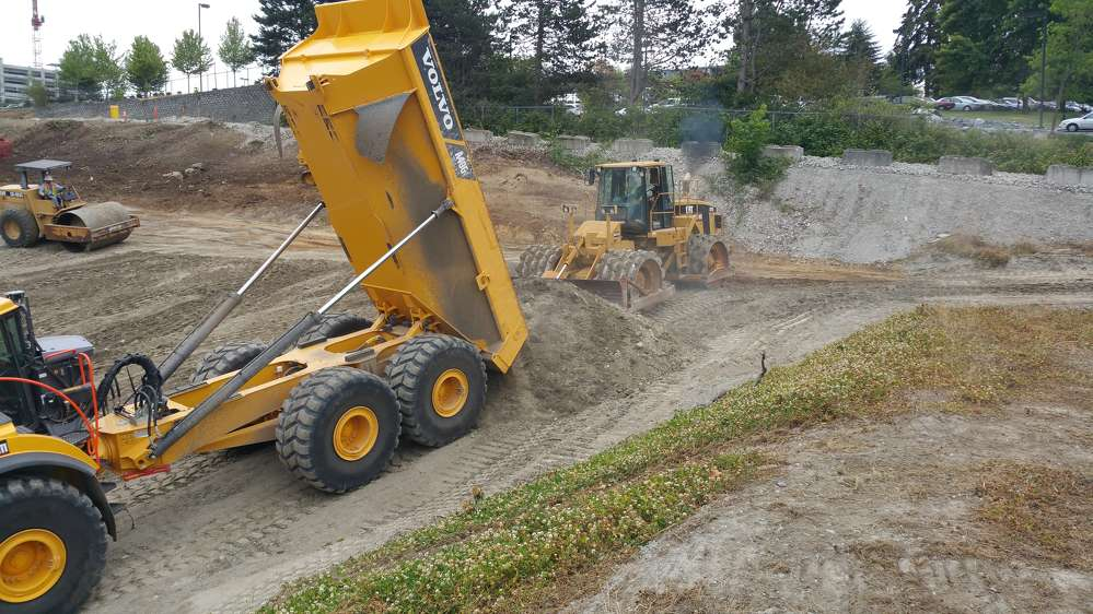 A Volvo A40G off-road dump truck and a Caterpillar 825G front loader with sheep's feet wheels work together to deposit and compact fill. (Ceccanti Inc. photo)