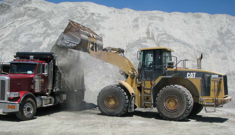 A Cat 980G wheel loader is used for loading trucks with aggregate.
