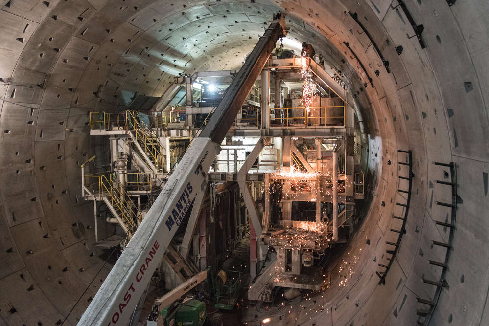 Crews use cutting torches to disassemble a section of the SR 99 tunneling machine's trailing gear inside the tunnel in Seattle. (WSDOT photo)