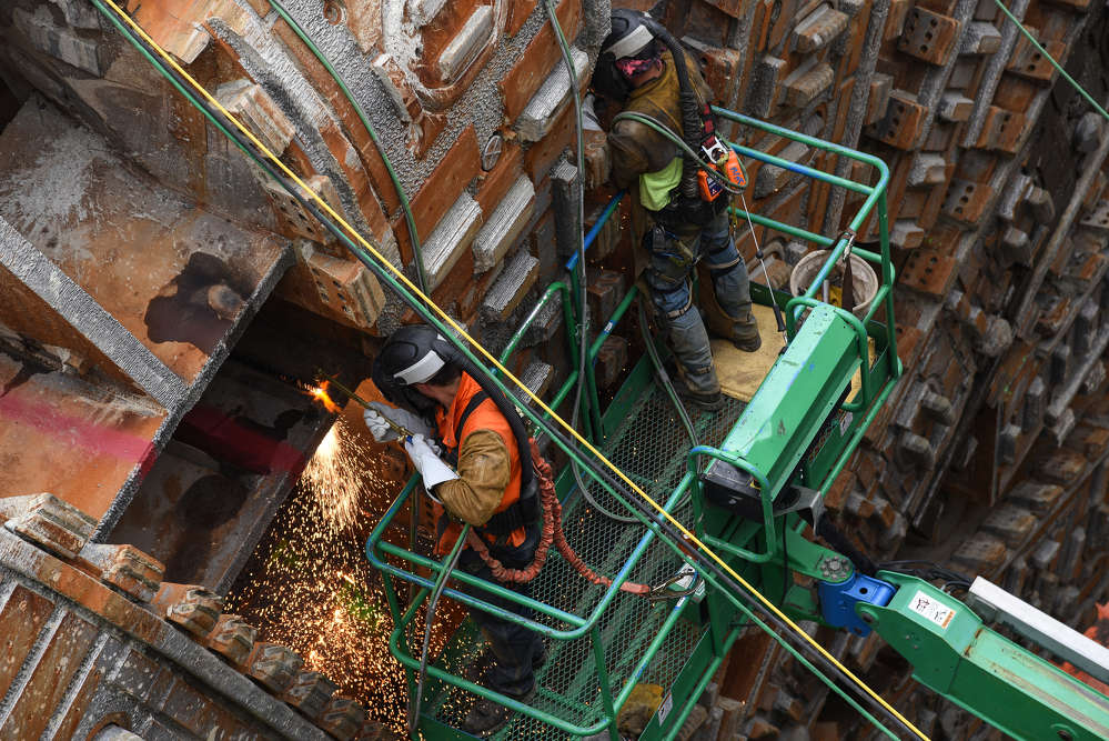 In this May 2017 photo, welders working for Seattle Tunnel Partner cut a section of the SR 99 tunneling machine's cutterhead in preparation for its removal from the disassembly pit near Seattle Center. (WSDOT photo)