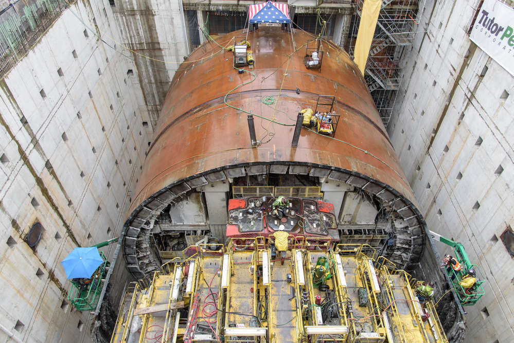 This May 2017 photo shows crews' progress on removing the SR 99 tunneling machine's cylindrical steel shield inside the disassembly pit near Seattle Center. This view looks north, with the cutterhead at the machine's far end, beneath the small rain canopy. (WSDOT photo)
