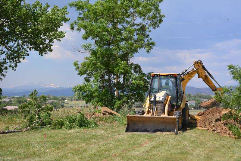 An operator from Zak Dirt Inc. uses a backhoe loader to dig a section of the new Colorado Front Range Trail-Loveland to Fort Collins Connection along Carpenter Road on June 22.
