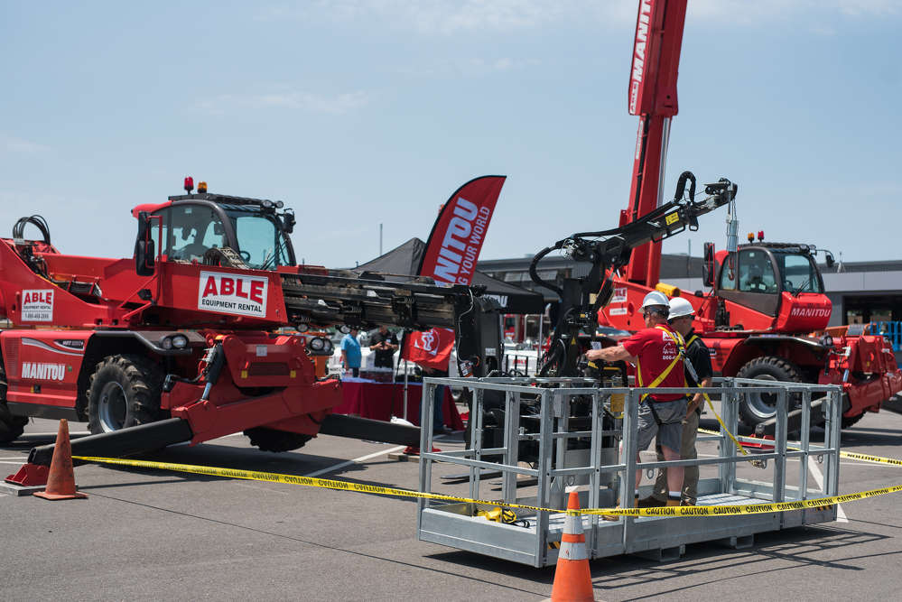 Philippe Bisson (R), senior business development manager of Manitou, gives Howie Hawkesworth, ABLE's facilities manager, some tips about the MRT 3255 rotating telehandler.