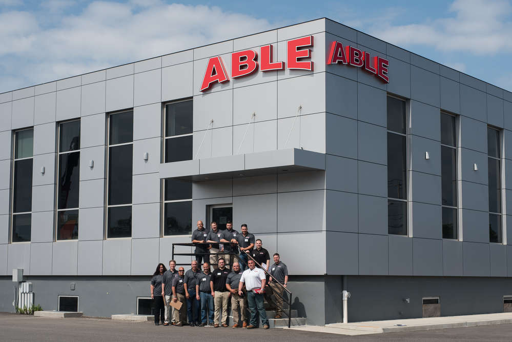 The ABLE sales team: (L-R, on stairs) are Joe Leinwol, Ryan Hubschmitt, Nick Webb, Matt Cohan, Jim Bruno and Jonathan Fieles. (L-R, front row) are Heli Howe, Frank Szyskowski, Lou Sordini, Chris Esposito, Rich Mummendey, Rob Bowser, Juan Diaz and Dino Kalogeropolous.